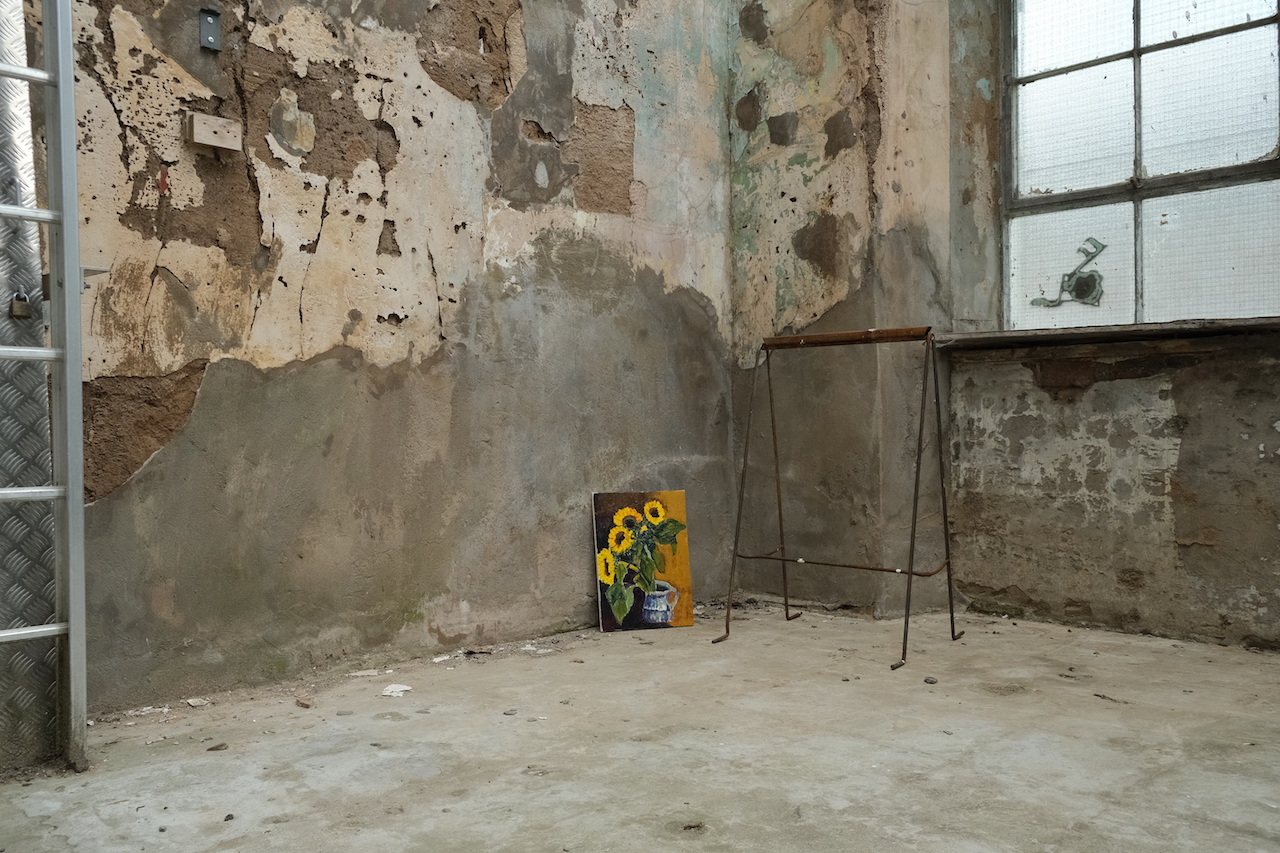 A painting of a bunch of sunflowers is placed on the floor, at the corner of a room with unpainted, run-down walls.